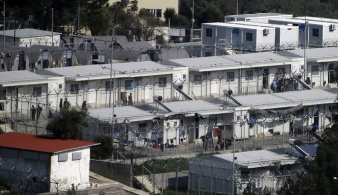 In this photo taken on Wednesday, March 15, 2017 migrants walk at the Moria refugee detention center on the northeastern Greek island of Lesbos. The waters off northern Lesbos once resounded to the shrieks of the drowning, the whine of outboard motors as refugees struggled to reach Europe alive, and the thudding of rescue helicopter engines. A million people crossed the straits between Turkey and Greeces eastern Aegean islands in the year before March 20, 2016, and hundreds drowned. About half of those who made it landed on this island.  (AP Photo/Thanassis Stavrakis)
