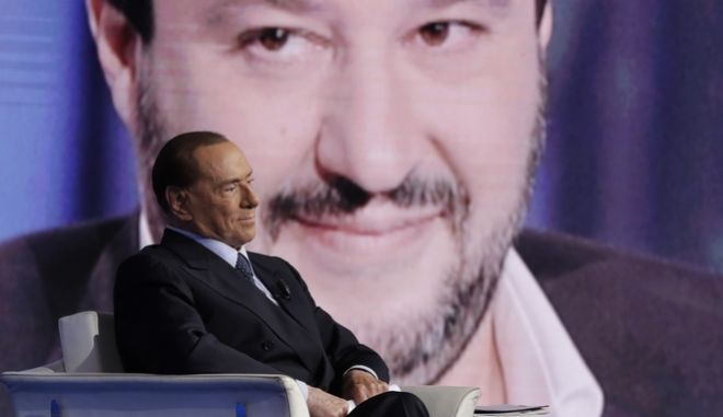 Italian former Prime Minister and Forza Italia (Go Italy) party leader, Silvio Berlusconi, is backdropped by Northern League party leader Matteo Salvini during the recording of the Italian state television RAI, Porta a Porta (Door To Door) talk show in Rome, Thursday, Jan. 11, 2018. (AP Photo/Andrew Medichini)