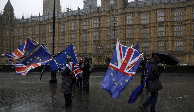 Anti-Brexit remain in the European Union supporters take part in a protest under a heavy rain outside the House of Parliament in London, Tuesday, March 12, 2019. Britain's attorney general punctured Prime Minister Theresa May's hopes of winning backing for her Brexit deal Tuesday, saying last-minute changes secured from the European Union didn't give Britain the power to cut itself free of ties to the bloc. (AP Photo/Matt Dunham)