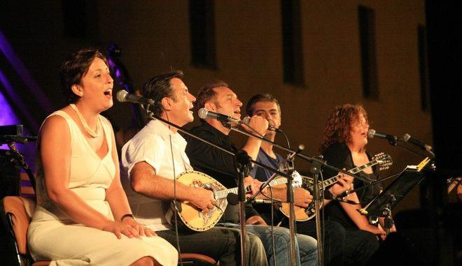 ΑΡΓΟΣ-Η Μουσική παράσταση «μπουζούκι & λαϊκό τραγούδι» το Σάββατο 18 Αυγούστου 2012 στις Στρατώνες  του Καποδίστρια ενθουσίασε τους θεατές και χειροκροτήθηκε θερμά. Στην εκδήλωση παραβρέθηκε ο δήμαρχος  Άργους βΜυκηνών Δημήτρης Καμπόσος , ο πρόεδρος  της ΚΕΔΑΜ Νίκος Γκαβούνος  και ο δημοτικός σύμβουλος Γιώργος Σαρρής. Την μουσική εκδήλωση οργάνωσε η ΚΕΔΑΜ και τραγούδησαν: Γεράσιμος  Ανδρεάτος,Άννα Καραγεωργιάδου,Μαργαρίτα Καραμολέγκου και ο Σπύρος Κουτσοβασίλης, στο μπουζούκι ο συμπολίτης μας Βαγγέλης Τρίγκας μουσικοί: Θανάσης Σοφράς  (κοντραμπάσο),Βασίλης Κετεντζόγλου  (κιθάρα).Θοδωρής Μπρουτζάκης  (πιάνο), Παναγιώτης Στεργίου  (μπουζούκι). Ήταν μια ιστορική αναδρομή με τραγούδια και οργανικά κομμάτια, που  αναδεικνύουν το ρόλο που έπαιξαν οι δεξιοτέχνες του μπουζουκιού, στη δημιουργία του ρεμπέτικου τραγουδιού και στη μετέπειτα εξέλιξή του, σε λαϊκό και  έντεχνο λαϊκό, ως τον Χατζιδάκι και τον Θεοδωράκη. Τα τραγούδια παίχτηκαν με τη χρονολογική σειρά που ηχογραφήθηκαν, ενώ τα σχόλια που έκανε ο Βαγγέλης Τρίγκας ενδιάμεσα, έδιναν στην παράσταση  μια ακαδημαϊκή διάσταση, βοηθώντας το θεατή να κατανοήσει την εξέλιξη του ρεμπέτικου β λαϊκού και έντεχνου λαϊκού στις τρεις πρώτες δεκαετίες (1930 β 1960) .( EUROKINISSI-ΒΑΣΙΛΗΣ ΠΑΠΑΔΟΠΟΥΛΟΣ)