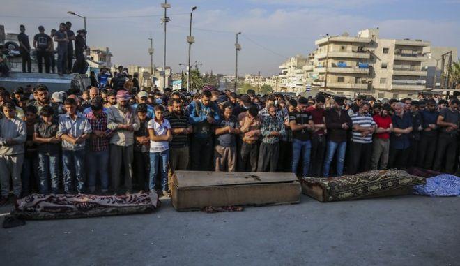 Άνθρωποι πενθούν για τους νεκρούς του πολέμου στη Συρία τον περασμένο Οκτώβριο