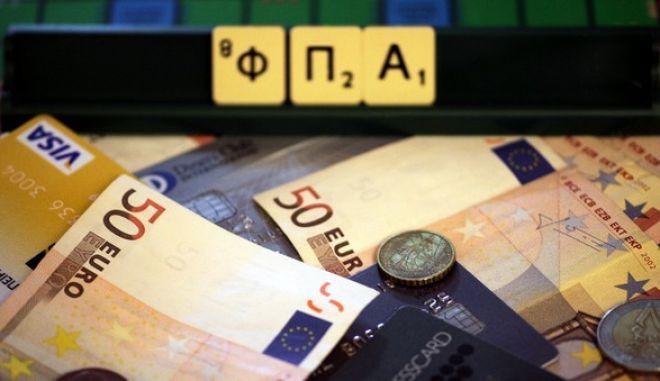 Η λέξη ΦΠΑ σχηματισμένη από γράμματα του επιτραπέζιου παιχνιδιού Scramble περιτρυγιρισμένη από νομίσματα και χαρτονομίσματα του ευρώ και πιστωτικές κάρτες. (EUROKINISSI/ΓΙΩΡΓΟΣ ΚΟΝΤΑΡΙΝΗΣ)