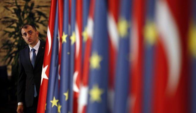 Ευρωπαίος αξιωματούχος μπροστά σε ευρωπαϊκές και τουρκικές σημαίες