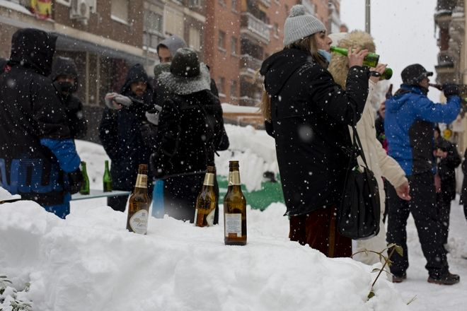 People keep their beer bottles cool in the snow outside a bar during a heavy snowfall in central Madrid, Spain, Saturday, Jan. 9, 2021. An unusual and persistent blizzard has blanketed large parts of Spain with snow, freezing traffic and leaving thousands trapped in cars or in train stations and airports that had suspended all services as the snow kept falling on Saturday. The capital, Madrid, and other parts of central Spain activated for the first time its red weather alert, its highest, and called in the military to rescue people from cars vehicles trapped in everything from small roads to the city's major thoroughfares. (AP Photo/Paul White)