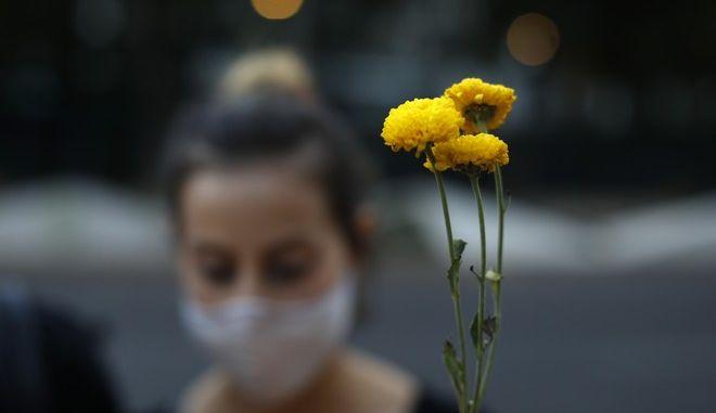 Διαδηλώτρια στις ΗΠΑ κρατάει λουλούδια