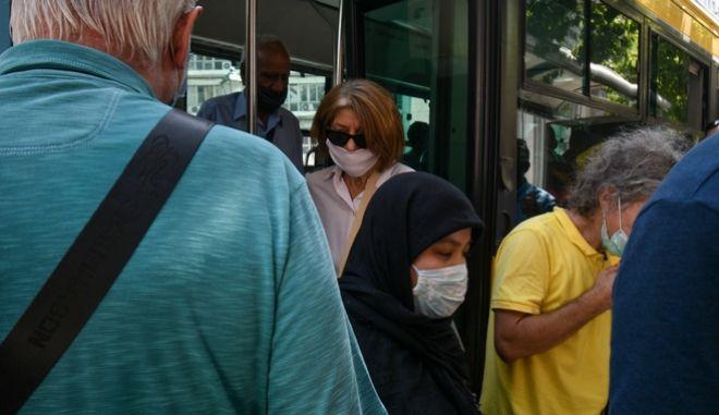 Επιβάτες με μάσκα αποβιβάζοντα από λεωφορείο του ΟΑΣΑ