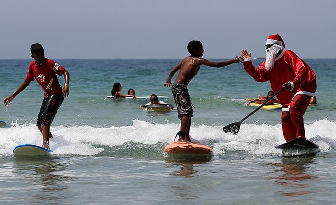 Carlos Bahia, dressed as Santa Claus, jokes with a child as they surf at the Maresias beach, in the state of Sao Paulo December 9, 2014. In the Southern Hemisphere summer starts on December 1, so while countries in the north are experiencing a white Christmas with grey skies, those in the south are busy surfing and sunbathing in temperatures just shy of 100 degrees Fahrenheit (38 degrees Celsius). Picture taken December 9, 2014.  REUTERS/Nacho Doce (BRAZIL - Tags: SOCIETY ENVIRONMENT) - RTR4IPOQ