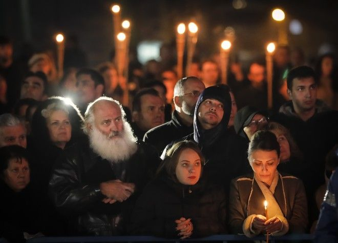 People watch the funeral service for the late Romanian King Michael in Curtea de Arges, Romania, Saturday, Dec. 16, 2017. Tens of thousands of Romanians have joined European royals to pay their respects to late King Michael who is being given a state funeral in the capital Bucharest and Curtea de Arges.(AP Photo/Vadim Ghirda)