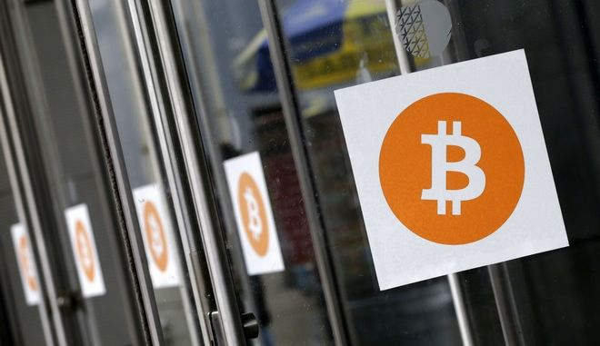 In this April 7, 2014 file photo, Bitcoin logos are displayed at the Inside Bitcoins conference and trade show in New York.  About $13 million in bitcoins will be auctioned in Sydney in June after Australian police confiscated the digital currency as proceeds of crime, an official said Tuesday, May 31, 2016. (AP Photo/Mark Lennihan, File)