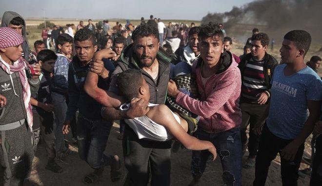 Παλαιστίνιοι διαδηλωτές μεταφέρουν τραυματία από ισραηλινά πυρά