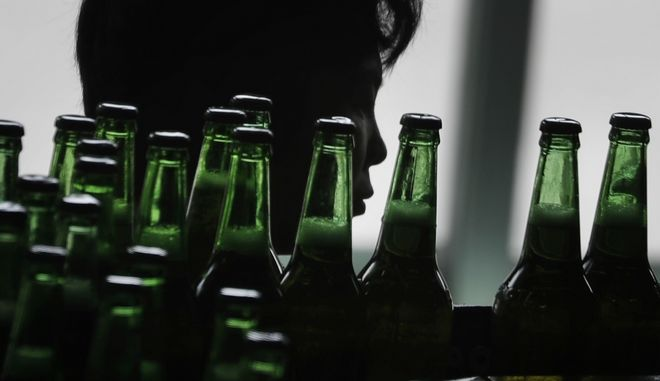 In this Wednesday, July 26, 2017, photo, a worker is seen in silhouette as bottles of beer pass her on a conveyor belt at the Taedonggang Brewery on Wednesday, July 26, 2017, in Pyongyang, North Korea. Taedonggang beers are generally reputed to be world-class, which is a matter of national pride among many North Koreans. (AP Photo/Wong Maye-E)