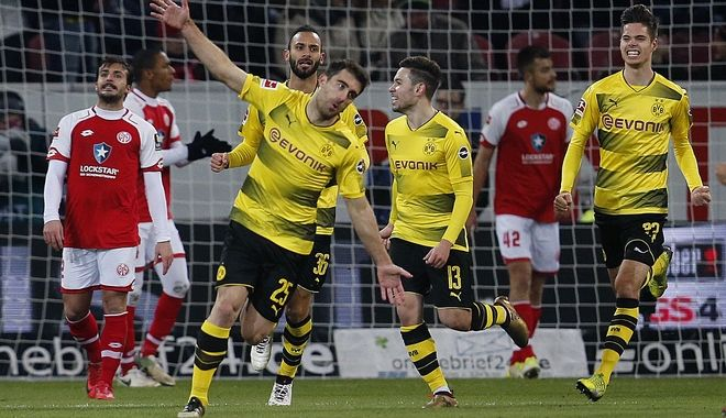 Dortmund's Sokratis, left, celebrates his side's opening goal during a German first division Bundesliga soccer match between FSV Mainz 05 and Borussia Dortmund in Mainz, Germany, Tuesday, Dec. 12, 2017.(AP Photo/Michael Probst)