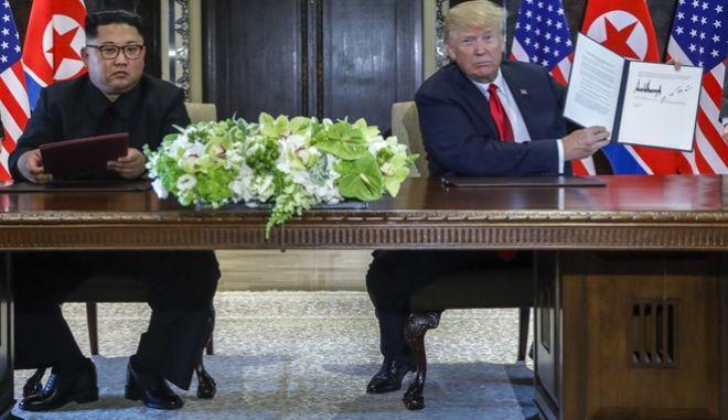Ο Ντόναλντ Τραμπ επιδεικνύει το έγγραφο που υπέγραψε με τον Κιμ Γιονγκ Ουν