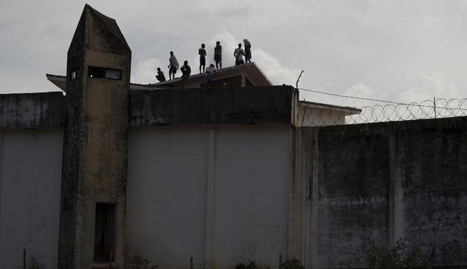 Κρατούμενοι στέκονται στην οροφή κτιρίου των φυλακών της Alcacuz στη Βραζιλία