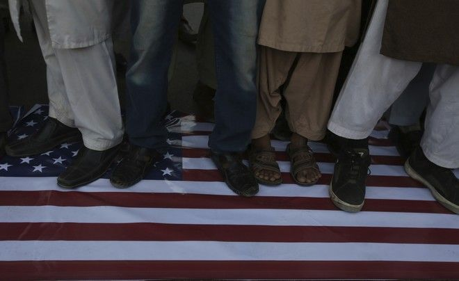 Supporters of Pakistani religious party Jamaat-e-Islami stand on a representation of the US flag during a rally against United States and Israel in Karachi, Pakistan, Thursday, Dec. 7, 2017.  Some hundreds of Islamists have rallied in major cities across Pakistan, condemning U.S. President Donald Trump for declaring Jerusalem as Israel's capital. (AP Photo/Fareed Khan)