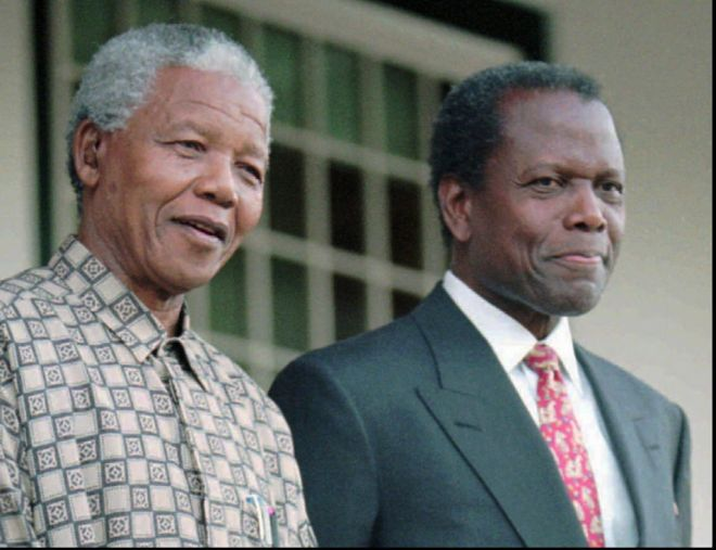 South African President Nelson Mandela smiles with popular actor Sidney Poitiers as he talks at a news conference in Cape Town, Friday, May 17. 1996. Poitier is in South Africa starring in the leading role as Mandela, alongside Michael Caine, who plays former President F. W. de Klerk in
