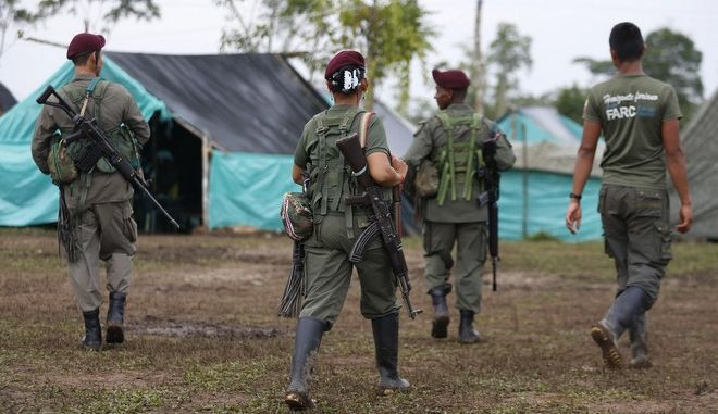 Revolutionary Armed Forces of Colombia, FARC, rebels walk in their camp in La Carmelita near Puerto Asis in Colombia's southwestern state of Putumayo, Tuesday, Feb. 28, 2017. March 1 was the deadline for the FARC to turn over 30 percent of their arms. But logistical delays setting up the rural camps where rebels are gathered has slowed the process. (AP Photo/Fernando Vergara)