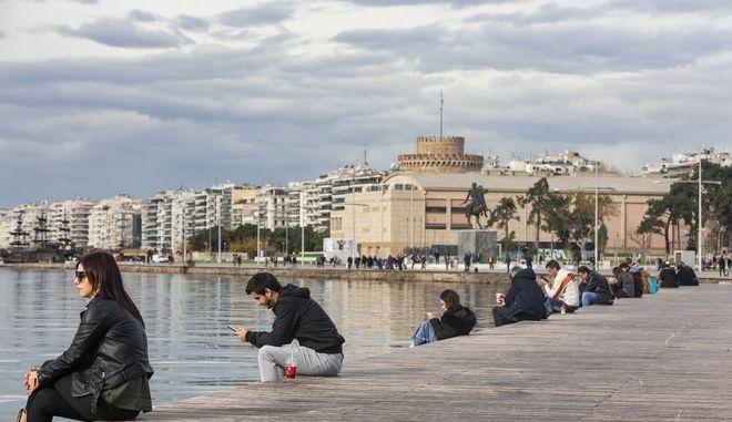 Κόσμος κάθεται στην παραλία Θεσσαλονίκης