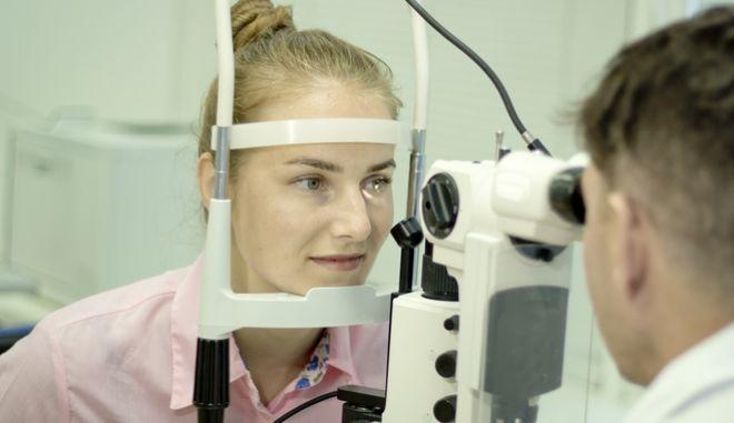 Γυναίκα κάνει εξετάσεις στον οφθαλμίατρο
