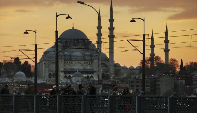 People walk across the bridge over the Golden Horn backdropped by the Suleymaniye Mosque in Istanbul, Saturday, April 15, 2017. Turkey is heading to a contentious referendum on Sunday April 16, on constitutional reforms to expand Turkey's President Recep Tayyip Erdogan's powers. (AP Photo/Emrah Gurel)