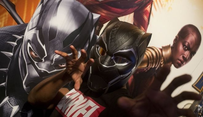 In this Tuesday, Feb. 20, 2018, photo Rafael Jordan models the Black Panther helmet from Hasbro at Toy Fair in New York. The helmet will be available in the fall for $99.99. (AP Photo/Mark Lennihan)