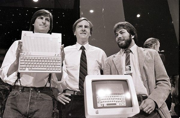 FILE - In this April 24, 1984, file photo, Steve Jobs, left, chairman of Apple Computers, John Sculley, center, president and CEO, and Steve Wozniak, co-founder of Apple, unveil the new Apple IIc computer in San Francisco. Apple has turned 40, and its a very different company from the audacious startup that Jobs and Wozniak launched in a Silicon Valley garage in 1976. (AP Photo/Sal Veder, File)