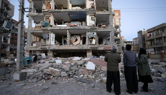 In this photo provided by the Iranian Students News Agency, ISNA, people look at destroyed buildings after an earthquake at the city of Sarpol-e-Zahab in western Iran, Monday, Nov. 13, 2017. A powerful earthquake shook the Iran-Iraq border late Sunday, killing more than one hundred people and injuring some 800 in the mountainous region of Iran alone, state media there said. (Pouria Pakizeh/ISNA via AP)