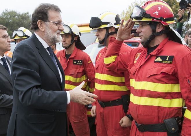 Spanish Prime Minister Mariano Rajoy, left, meets emergency personnel after a wildfire in Pontevedra, in the northwestern Spanish region of Galicia, Spain on Monday, Oct. 16, 2017. Authorities in Portugal and Spain say that nine people died over the weekend in hundreds of wildfires fanned by strong winds caused by a hurricane. (AP Photo/Lalo R. Villar)