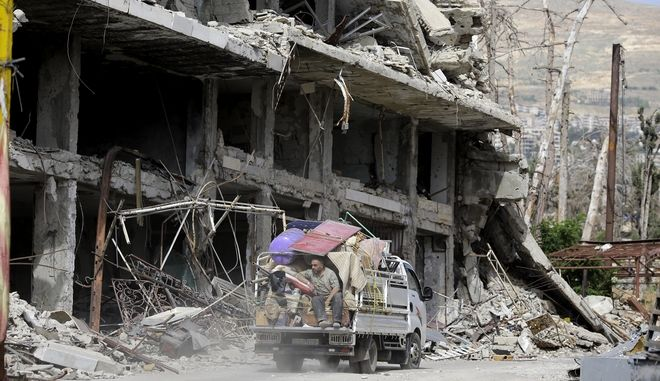 A Syrian man sits on the back of a truck after took some furniture from his destroyed house in the mountain resort town of Zabadani in the Damascus countryside, Syria, Thursday, May 18, 2017. (AP Photo/Hassan Ammar)