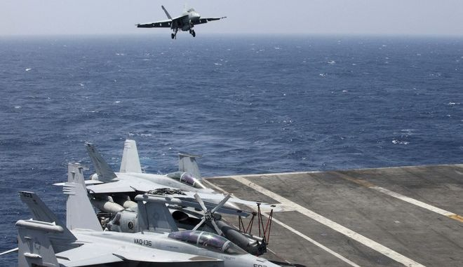 FILE - In this March 3, 2017 file photo, a U.S. Navy F18 fighter jet lands on the U.S. Navy aircraft carrier USS Carl Vinson (CVN 70) following a patrol off the disputed South China Sea. The USS Carl Vinson, which is steaming through the South China Sea, is just one of several high-profile displays of U.S. naval power as President Donald Trump's administration weighs options of how to reassure allies and respond to an assertive China. The current makeup of the aircraft carrier strike group suggests it may not carry out an anticipated freedom of navigation operation just yet. China has scoffed at U.S. patrols and stepped up its own presence. (AP Photo/Bullit Marquez, File)