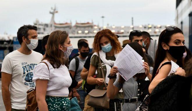 Πολίτες με μάσκα έτοιμοι για επιβίβαση σε πλοίο.