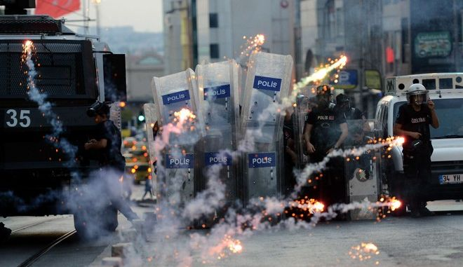 Turkish riot police use rubber bullets to disperse protesters as protestors fire fireworks at Kadikoy district in Istanbul on July 21, 2015, a day after a suicide bomb attack blamed on the Islamic State killed 32 people in the southern Turkish town of Suruc. Turkish police today fired tear gas and water cannon against hundreds of protesters who took to streets to condemn the deadly suicide attack in a border town, an AFP photographer reported.  AFP PHOTO /OZAN KOSE