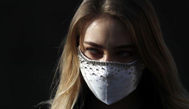 Γυναίκα η οποία φορά αυτοσχέδια μάσκα για προφύλαξη από τον κορονοϊό.