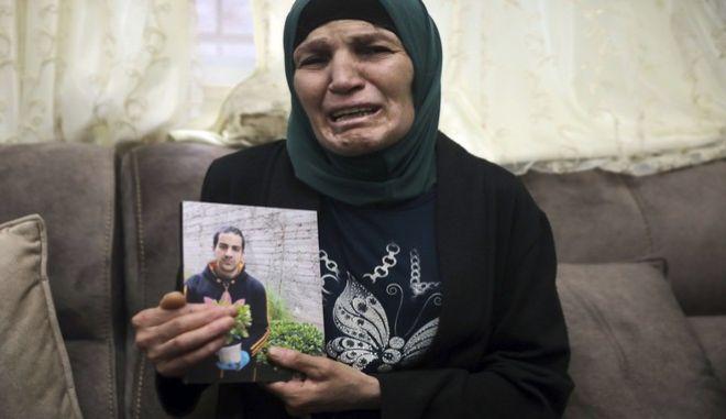 H Ράνα, η μητέρα του 32χρονου Ιγιάντ Χαλάκ, κρατάει την φωτογραφία του δολοφονημένου από Ισραηλινούς αστυνομικούς γιου της
