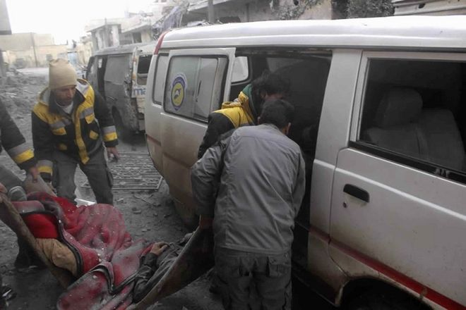 This photo released Tuesday Feb. 20, 2018, provided by the Syrian Civil Defense group known as the White Helmets, shows members of the Syrian Civil Defense group carrying a man who was killed during airstrikes and shelling by Syrian government forces, in Ghouta, a suburb of Damascus, Syria. Intense Syrian government shelling and airstrikes of rebel-held Damascus suburbs killed at least 100 people since Monday in what was the deadliest day in the area in three years, a monitoring group and paramedics said Tuesday. (Syrian Civil Defense White Helmets, via AP)
