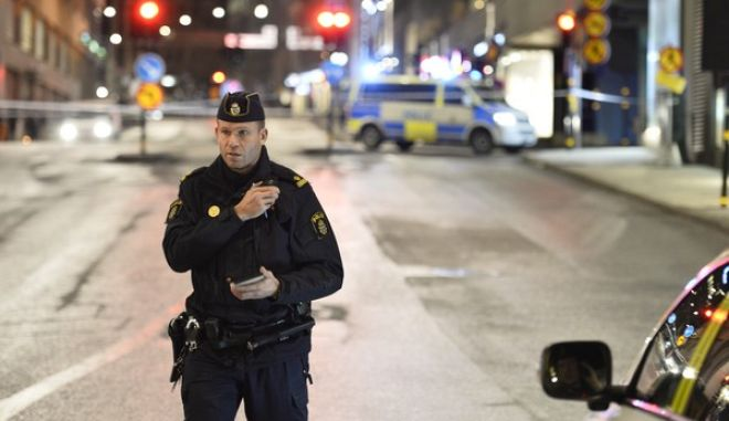 Police guard a roped off area near the shopping mall 'Moodgallerian' and a car tunnel in central Stockholm, Sweden, after an explosion Tuesday, Jan. 26, 2016. The explosion caused damage to a car and a building, but no injuries are reported. Police are investigating the cause of the explosion. (Marcus Ericsson/TT via AP) SWEDEN OUT