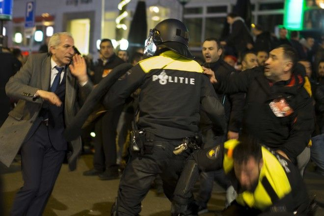 """Demonstrators battle with Dutch riot police after riots broke out near the Turkish consulate in Rotterdam, Netherlands, Sunday, March 12, 2017. Turkish Foreign Minister Mevlut Cavusoglu was due to visit Rotterdam on Saturday to campaign for a referendum next month on constitutional reforms in Turkey. The Dutch government says that it withdrew the permission for Cavusoglu's plane to land because of """"risks to public order and security."""" (AP Photo/Peter Dejong)"""