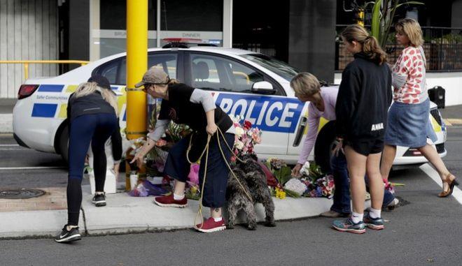 Περαστικοί αφήνουν λουλούδια για τους νεκρούς σε τζαμί στο Κράιστσερτς