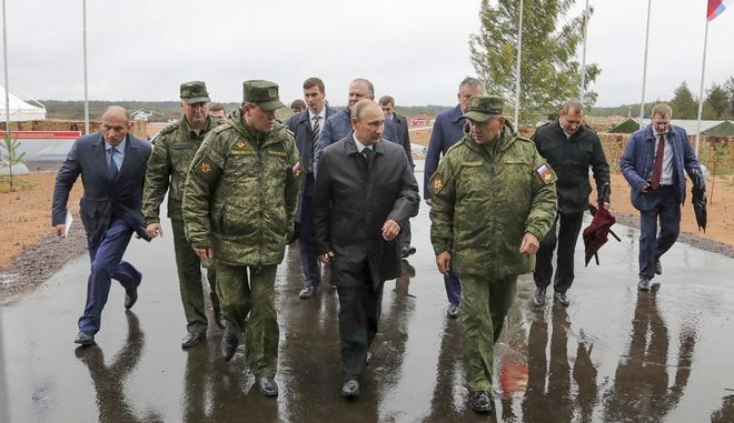 Russian President Vladimir Putin, center, Defence Minister Sergei Shoigu, right, and Chief of the General Staff of the Russian Armed Forces Valery Gerasimov, left, walk to attend a military exercise at a training ground at the Luzhsky Range, near St. Petersburg, Russia, Monday, Sept. 18, 2017. The Zapad (West) 2017 maneuvers have caused concern among some NATO members neighboring Russia, who have criticized a lack of transparency about the exercises and questioned Moscow's real intentions. (Sputnik, Kremlin Pool Photo via AP)