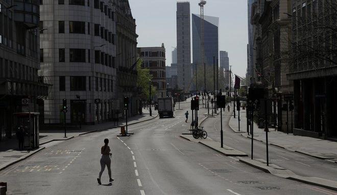 Άνθρωποι κάνουν τζόκινγκ σε δρόμο του Λονδίνου σε καιρό κορονοϊού
