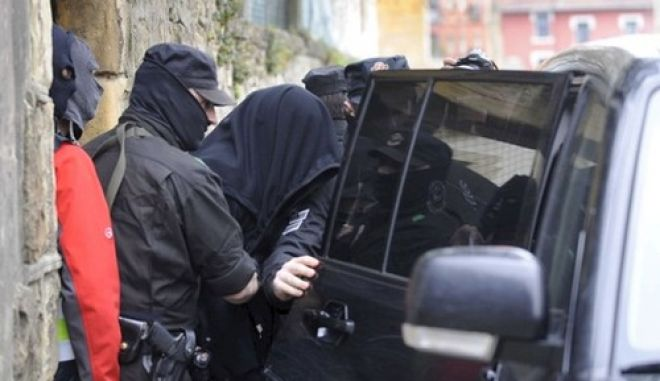 epa02080250 Masked members of Ertzaintza, the Basque regional police, escort an unidentified man after he was arrested as part of a police operation against Russian and Georgian mafia in Algorta, Basque Country, Spain, 15 March 2010.  Sixty nine persons have been arrested during the operation in at least six European countries, of which 24 have taken place in Spain, several of which in the Basque Country.  EPA/MIGUEL TONA