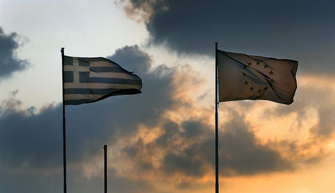 "A European Union flag flatters next to a Greek flag atop the Greek Ministry of Finance during sunset in central Athens, Greece June 5, 2015. Greece's government rejects an ""absurd"" and ""unrealistic"" proposal from creditors and hopes it will be withdrawn, Prime Minister Alexis Tsipras said on Friday as he called on lenders to accept a rival proposal from Athens instead. REUTERS/Yannis Behrakis  - RTX1FAYC"