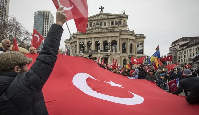 Demonstrators wave Turkish flags in front of the Old Opera House in Frankfurt, Germany, Wednesday, Jan. 24, 2018 as counter demonstrators shout anti-Turkish slogans to protest Turkish policy in northern Syria. (Frank Rumpenhorst/dpa via AP)