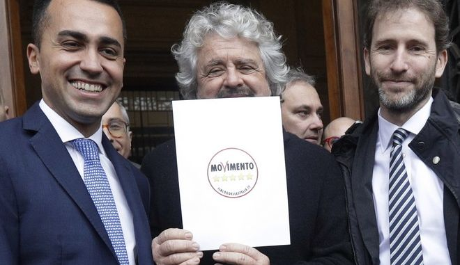 5-Star Movement founder Beppe Grillo, center, flanked by movement cofounder Davide Casaleggio, right, and lawmaker Luigi Di Maio, holds the official symbol they registered for the upcoming elections outside the Italian Interior Minister building, in Rome, Friday, Jan. 19, 2018. Italians vote March 4 in a parliamentary election, the vote is shaping up into a three way race between a weakened Democratic Party, the populist 5-Star Movement and the center-right, with Salvini's League vying for dominance with former Premier Silvio Berlusconi's Forza Italia. (AP Photo/Gregorio Borgia)