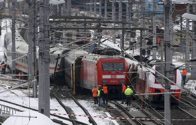 Rescuers  and railway workers stand at the scene of a train crash in Niklasdorf, Austria, Monday, Feb. 12, 2018. Two passenger trains collided near a station of Niklasdorf. Two passenger trains crashed in central Austria on Monday, killing one person and injuring more than 20 others, authorities said. One train hit the side of the other near the station in Niklasdorf, a town 60 kilometers (40 miles) north of Graz, said Graz police spokesman Leo Josefus. (AP Photo/Ronald Zak)