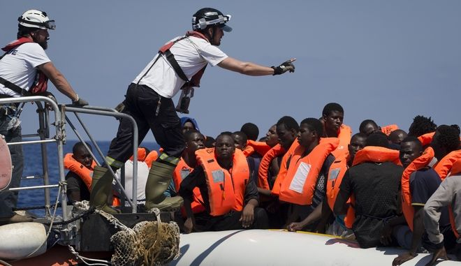 A rescuer instructs African migrants from a rescue boat during a rescue operation from the Aquarius vessel of SOS Mediterranee NGO and MSF (Doctors Without Borders) in the sea some 25 Nautical miles (29 miles, 46 kilometers) north of the Libyan coast, Sunday, Aug. 27, 2017. (AP Photo/Darko Bandic)