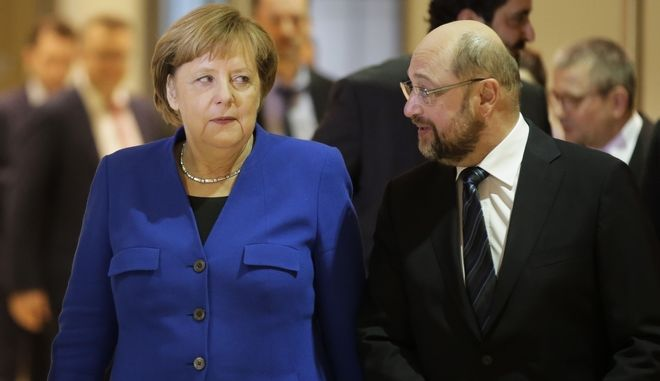 German Chancellor Angela Merke, left, and Social Democratic Party Chairman Martin Schulz, right arrives for a news conference after the exploratory talks between Merkel's Christian Democratic block and the Social Democrats on forming a new German government in Berlin, Germany, Friday, Jan. 12, 2018. (AP Photo/Markus Schreiber)