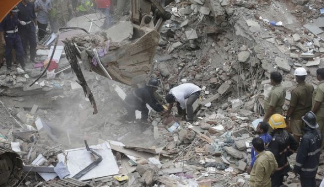 Rescuers work on the debris after a five-story building collapsed in the Ghatkopar area of Mumbai, India, Tuesday, July 25, 2017. A fire official says 11 people have been rescued and more are feared trapped.(AP Photo/Rafiq Maqbool)