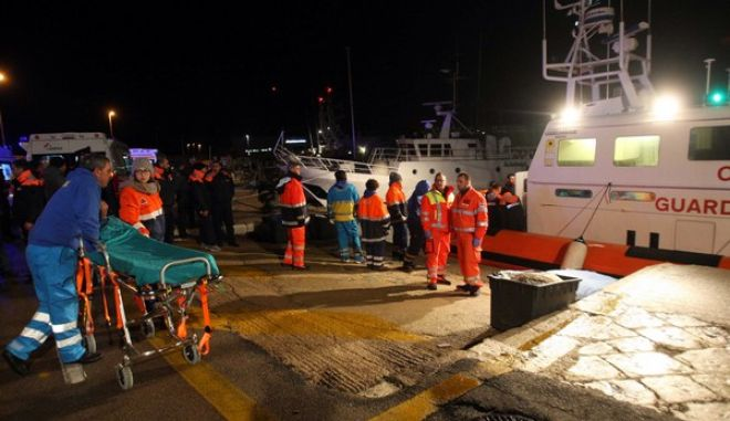 Paramedics wait for rescued passengers of the ferry that caught fire in the channel between Italy and Albania, at the Otranto harbor, near Lecce, southern Italy, Sunday, Dec. 28, 2014. Italian and Greek rescue crews battled gale-force winds and massive waves as they struggled Sunday to evacuate hundreds of people from a ferry on fire and adrift in the channel between Italy and Albania. At least one person died and two were injured. The fire broke out before dawn Sunday on a car deck of the Italian-flagged Norman Atlantic, traveling from the western Greek port of Patras to the Italian port of Ancona on the Adriatic, with 422 passengers and 56 crew members on board. (AP Photo/Ivan Tortorella)