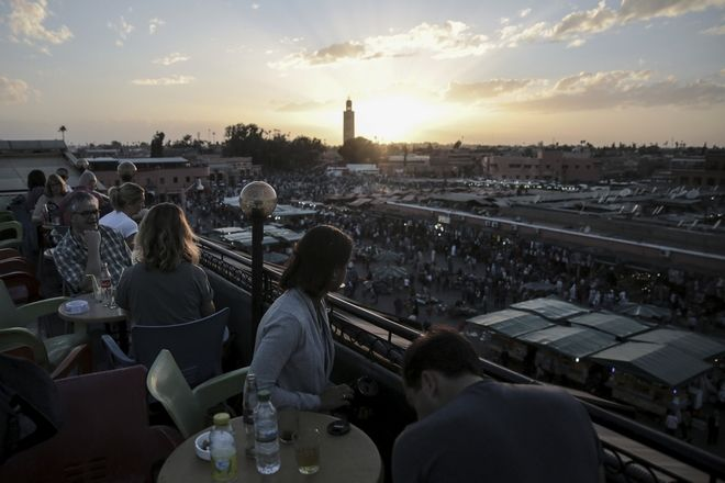Tourists observe the sunset from a rooftop in the landmark Jemaa el-Fnaa square, in Marrakesh, Morocco, Saturday, Nov. 5, 2016. The Climate Conference, known as the COP22, starts Monday in Marrakech and is expected to attract hundreds of participants and state representatives. (AP Photo/Mosa'ab Elshamy)